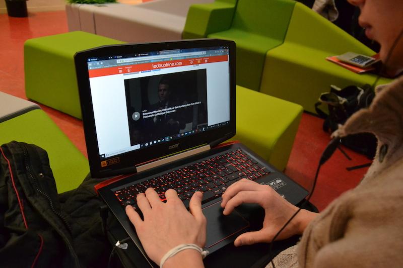 Lucas, mains sur le clavier de l'ordinateur, écouteurs sur les oreilles